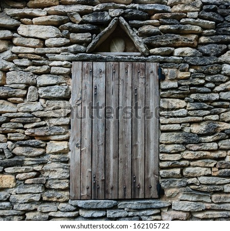Window with closed weathered wooden shutters on dry-stone wall. - stock photo