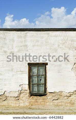Window with curtains on a boarded and abandoned adobe building. - stock photo