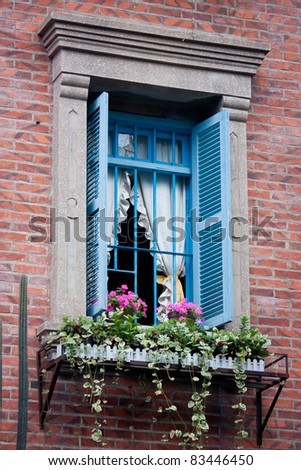 Window with flowers on brick wall - stock photo
