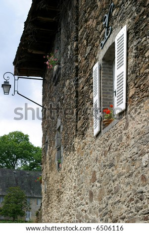 Window with Geraniums - side wall of a picturesque Limousin limestone house - stock photo