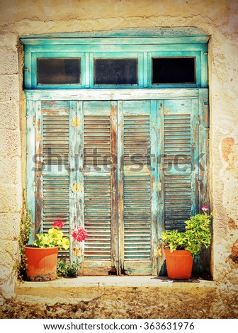 window with old wooden shutters and flowers in front , edited with a crossed processed bright look - stock photo
