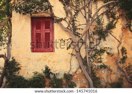 window with red shutter  of Anafiotika in town of Athens,Greece.Vintage style.