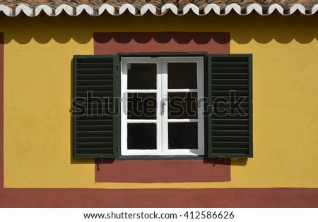 Window with shutters in yellow and red wall. Funchal, Madeira, Portugal - stock photo