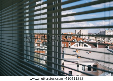 Window with white jalousie, close up. Behind the window is a city view - stock photo