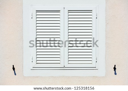 Window with white shutters - stock photo