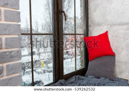 Window with windowsill with pillows and blanket in the bedroom in loft style, outside the window snow