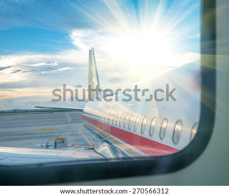 Windows and fuselage of a private airplane with tail against the cloudy sky - stock photo