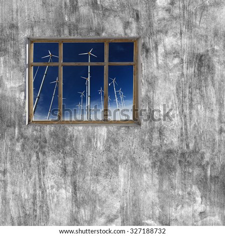 windows frame on cement wall and view of wind turbine  - stock photo