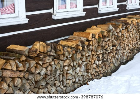 Windows of a traditional country cottage house with firewood logs  - stock photo