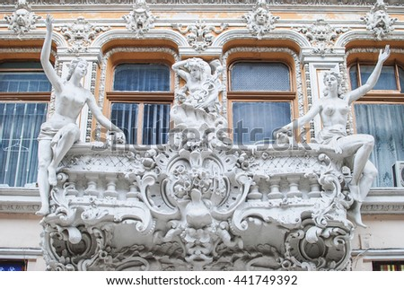 Windows of an ancient house with frsetwork statue on the balcony (facade) - stock photo