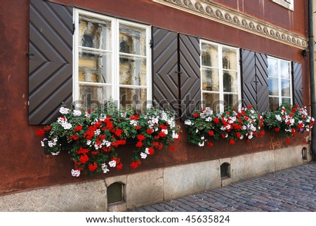 windows of antique house decorated with flowers - stock photo