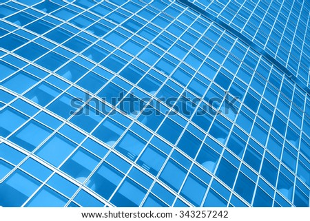 Windows of modern office building - architectural background. Toned in the blue color - stock photo