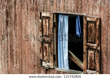 Windows of old, wooden cottage in the countryside - stock photo