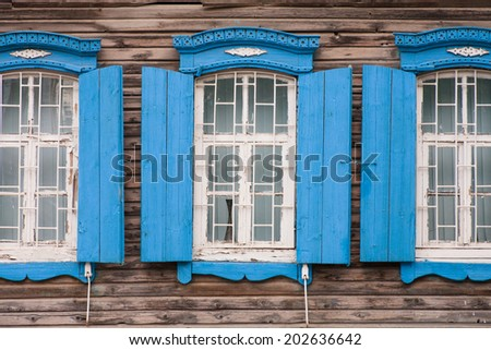Windows of old, wooden cottage in the countryside. Old Windows in Wooden Frame from a traditional Russian house - stock photo
