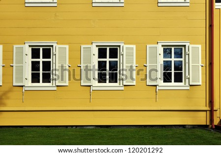 windows with shutters on yellow house - stock photo