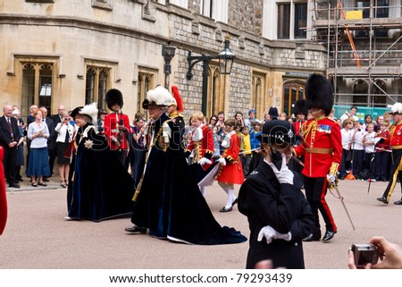 WINDSOR, UK- JUNE 13: Her Majesty Queen Elizabeth and Prince Phillip Duke of Edinburgh, in the robes of the Most Noble Order of the Garter with page boys. Windsor Castle June 13, 2011 in Windsor UK - stock photo