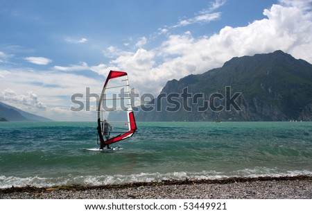 Windsurfer on a lake with mountains as a background - stock photo