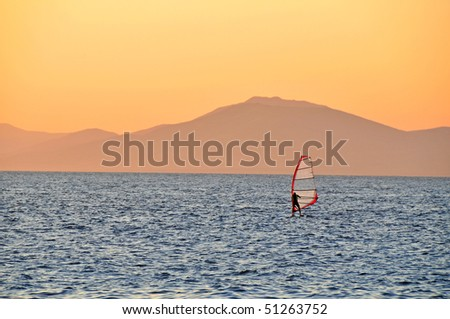windsurfer   sailing on a sunset - stock photo