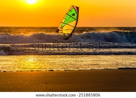 Windsurfer speeding fast against the sunset - stock photo