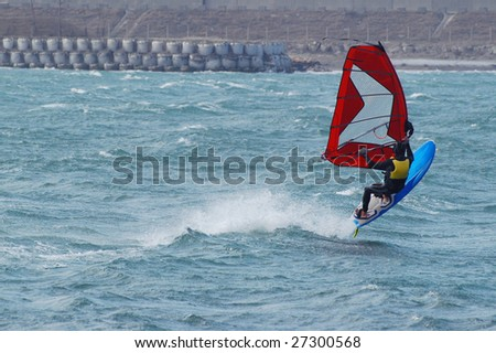 windsurfer with bright colored sail on Algarve blue water - stock photo