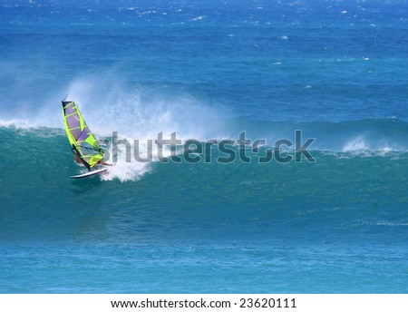 Windsurfer with green sails shooting down an ocean wave