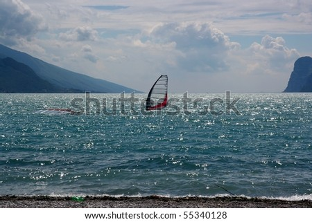 Windsurfer with red sails on a lake with mountains as a background - stock photo