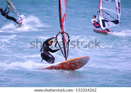 Windsurfing on a beach of Mediterranean sea - stock photo