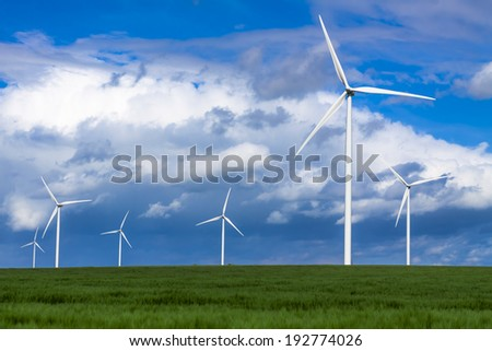 Windturbines in a green field generate sustainable energy - stock photo