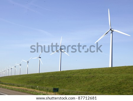 Windturbines on a dike in the Netherlands near a motorway - stock photo