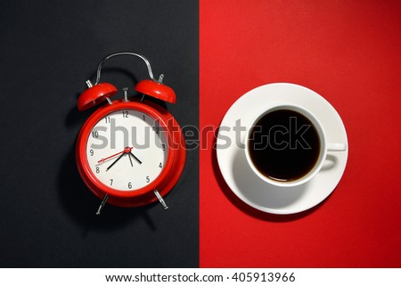 windup alarm clock red and white coffee Cup on a black and red background - stock photo