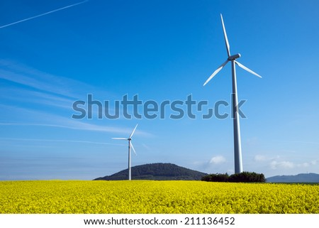 Windwheel and rapeseed in Germany - stock photo