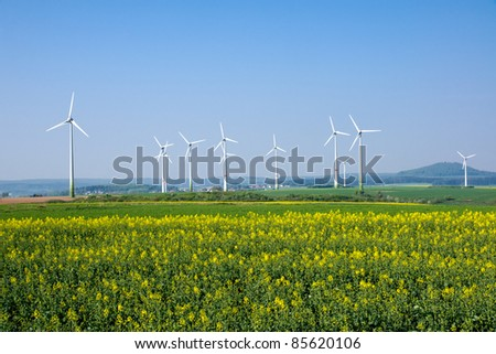 Windwheels and a rapeseed field in rural Germany - stock photo