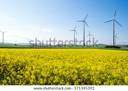 Windwheels and a yellow rapeseed field seen in Germany - stock photo