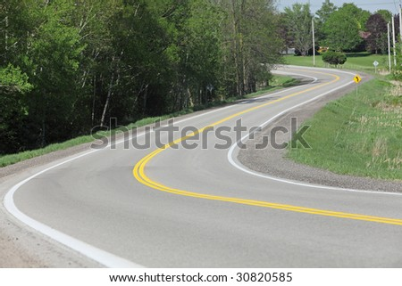 Windy rural road lined with trees and grass. - stock photo