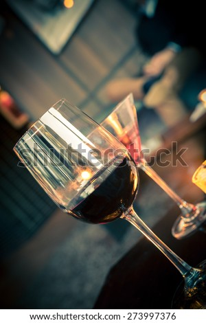 Wine and cocktail glasses in lounge with warm light - stock photo