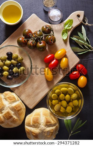 Wine appetizer set. Antipasti Platter of baked ham, red and yellow Grape Tomatoes, Black Sicilian tomatoes, black and green olives, the leaves of the olive tree, salt and pepper, bread turtle. - stock photo