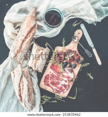 Wine appetizer set. Glass of red wine, vintage dinnerware, baguette broken into pieces, dried tomatoes, olives, smoked meat and arugula on a rustic wooden board over a dark background. Top view  - stock photo