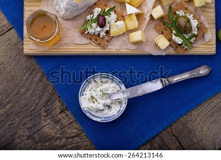 Wine appetizers set: cheese, olives and grapes on a dark rustic wooden background - stock photo