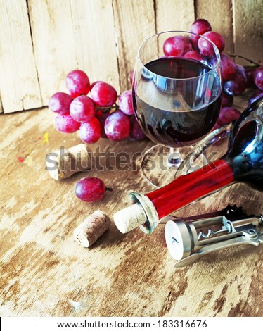 wine background with bottle of  red wine and glass on a old wooden table - stock photo
