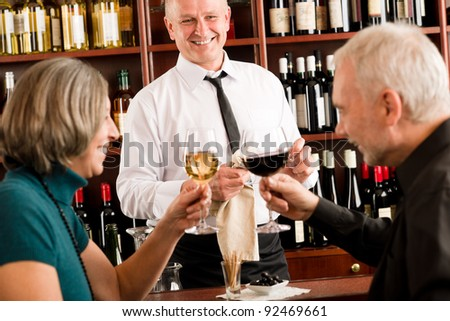 Wine bar senior couple enjoy drink professional barman pour glass - stock photo