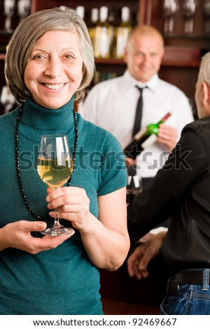 Wine bar senior woman manager enjoy drink smiling barman discussing - stock photo