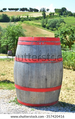 Wine barrel against rural Italian landscape - stock photo