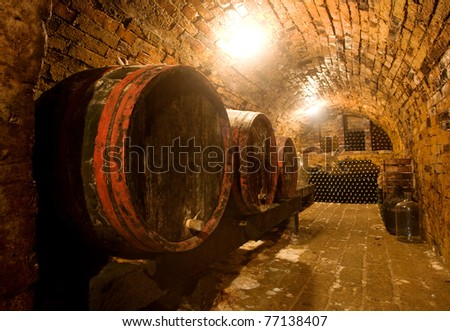 Wine barrels and bottles in a traditional cellar . Warm colors, wide angle view. - stock photo