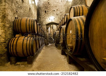 Wine barrels stacked in the old cellar of the winery - stock photo