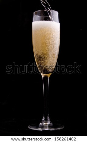 Wine being poured into a glass on black background - stock photo
