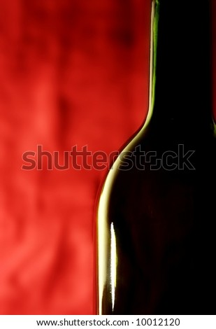 wine bottle against a red background - stock photo