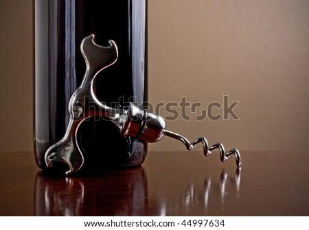 Wine bottle and corkscrew in a dark wine cellar - stock photo
