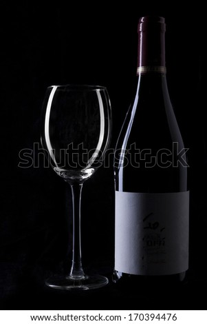 Wine bottle and empty glass silhouette on black background - stock photo
