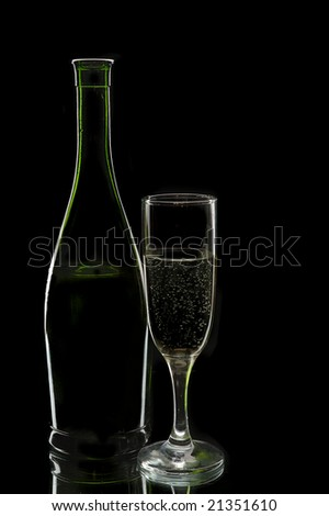 Wine bottle and glass against a black background - stock photo