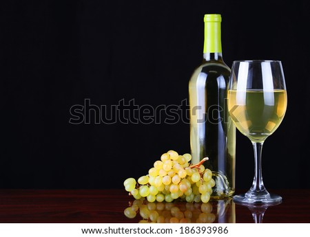 Wine Bottle and Glass of White Wine with Fresh Grapes over black background. - stock photo